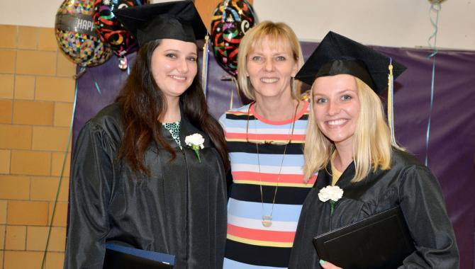 Two graduates with teacher