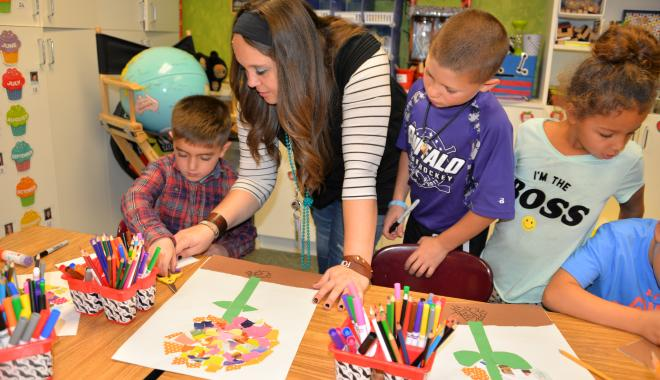 Teacher with students doing art projects