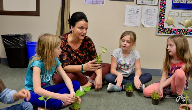 Discovery teacher with students discussing plants
