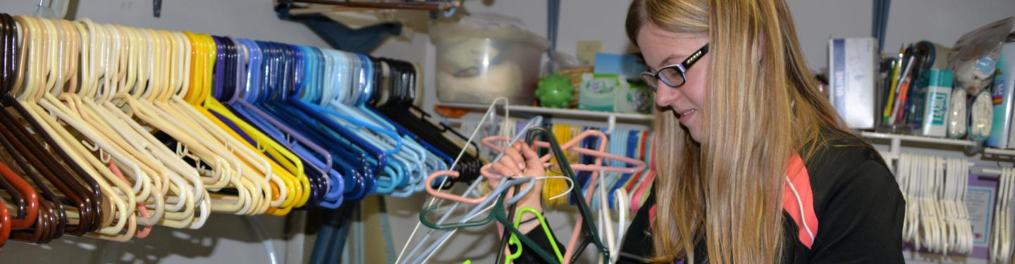 student sorting clothes hangers