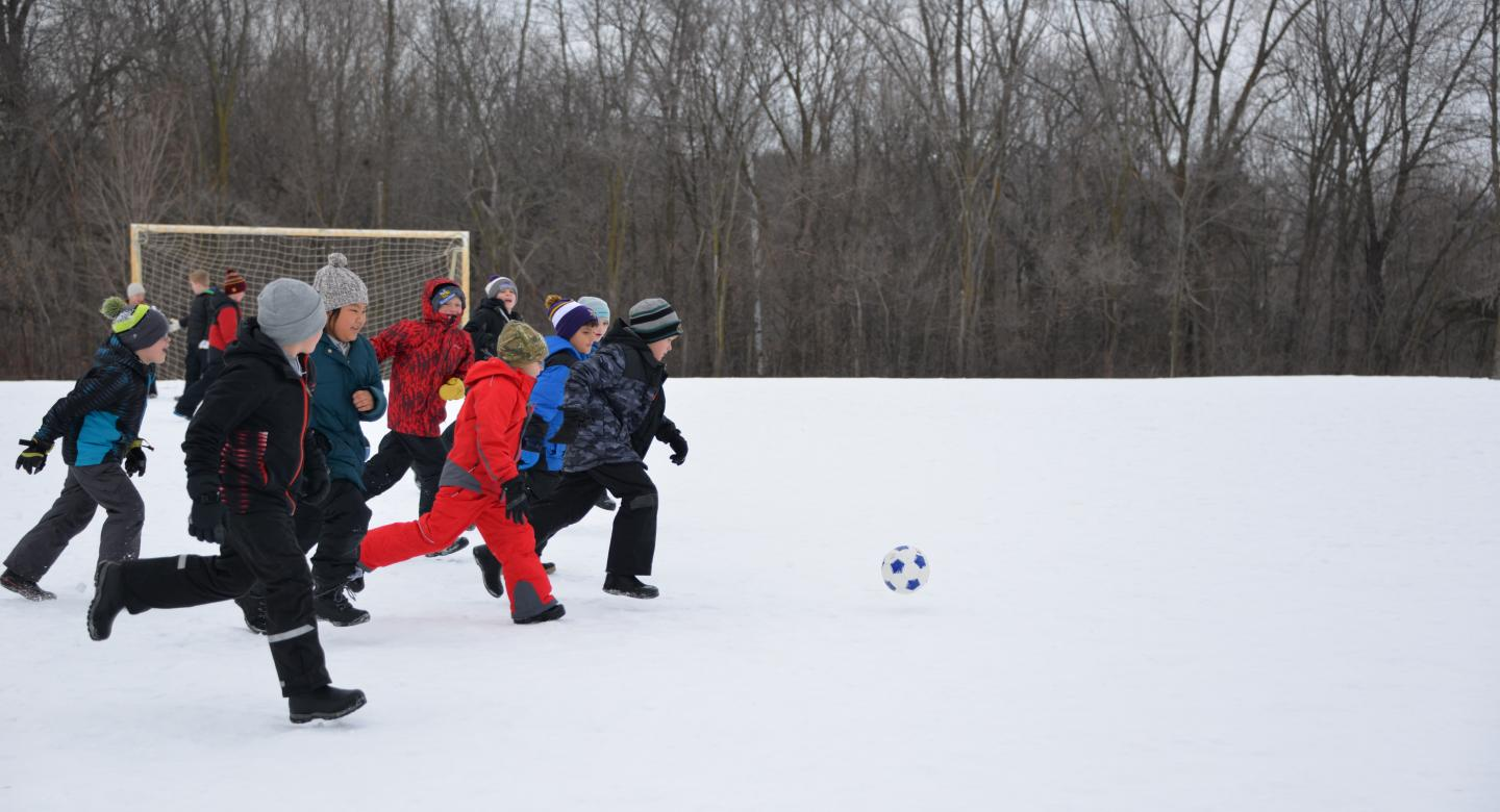 kids playing soccer in the snow