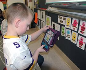 1st grader with iPad using learning apps